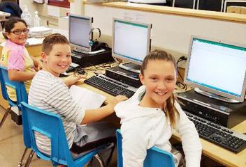 Three students smiling while using computers at Goshen Intermediate School.