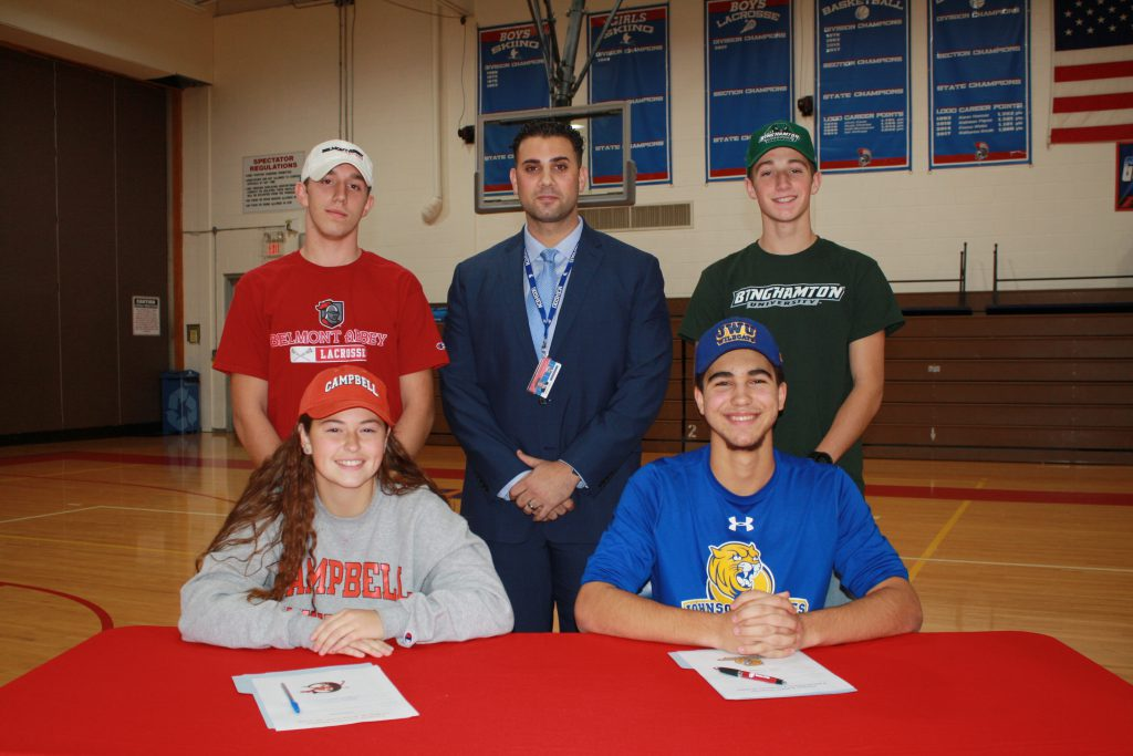 Four students and one adult behind table smiling