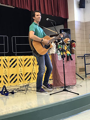 Kyle Dine plays guitar on stage at the elementary school.