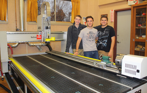 Students stand beside CNC machine.