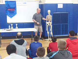 Physical Education Teacher Robert McIntee uses a skeleton to instruct participants in the gym.