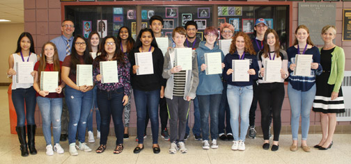 The Intro to Latin class smiles at the camera with certificates of achievement.