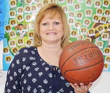 Physical Education Teacher Kathy Magid smiles while holding a basketball.