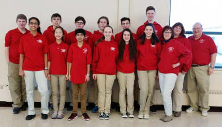 The Science Olympiad team and coaches in their team uniforms smile at the camera.