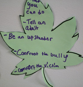 A green paper leaf with antibullying sentiments written on it.