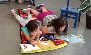 Two girls lay on a blanket together reading.