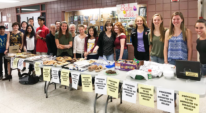 Smiling students stand behind a table holding baked goods such as donuts and cookies.