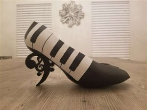 Shoe with piano keys painted on it in black and white.