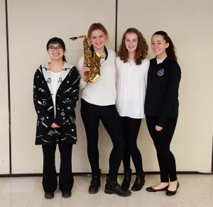 Students smiling, one holding a saxophone.