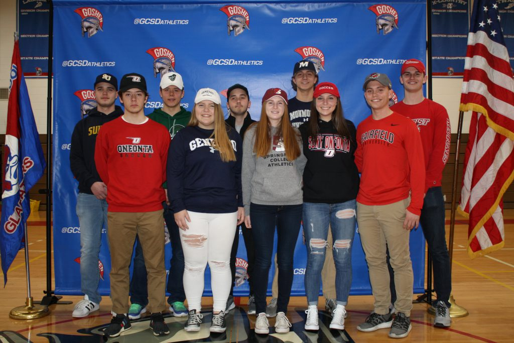 Group of students smiling wearing college attire and hats.