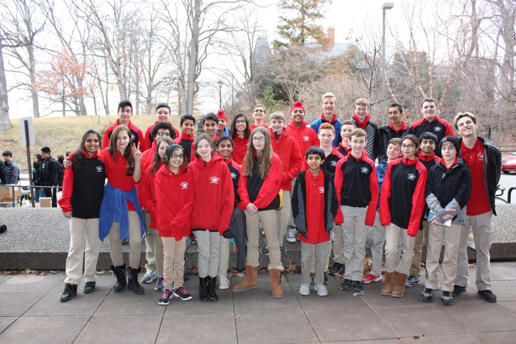Group photo of smiling students wearing red.
