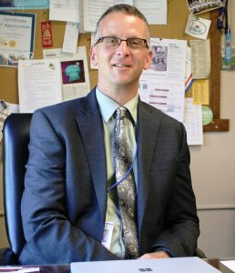 Dr. Kotes sits in his office wearing a suit and tie.