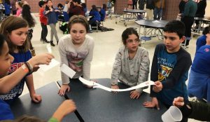 Students create a bridge with paper and paper clips.
