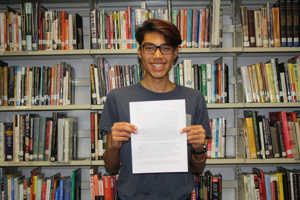 Teenage boy in front of book shelf holding paper