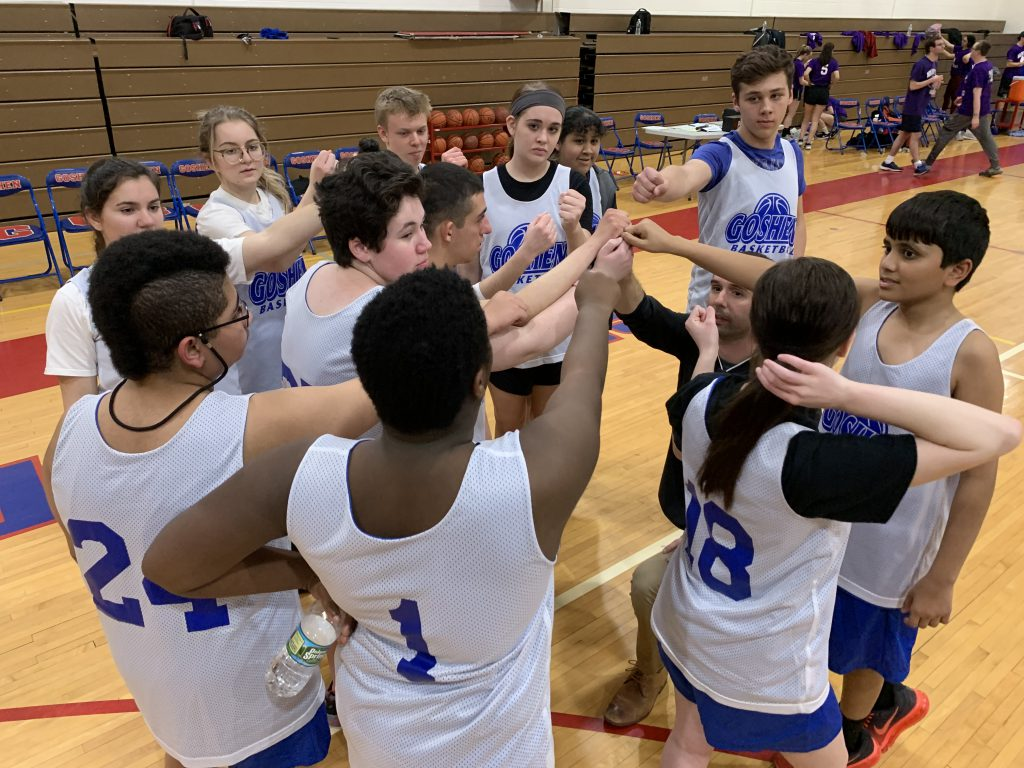 Photo of high school students in basketball uniforms touching fists