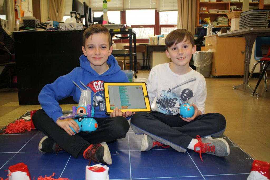 Two boys sitting on mat with robots and tablet.