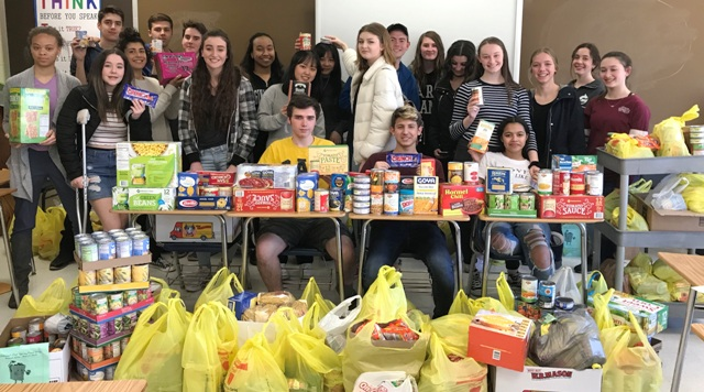 Photo of high school students with bags of canned food