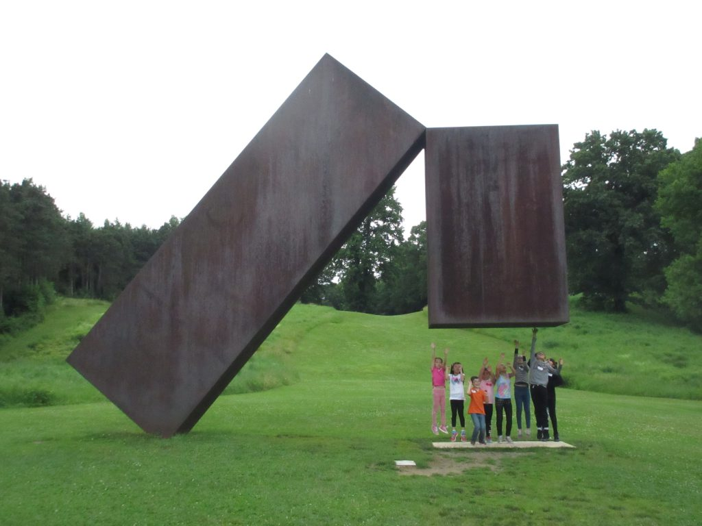 Students beneath a giant sculpture