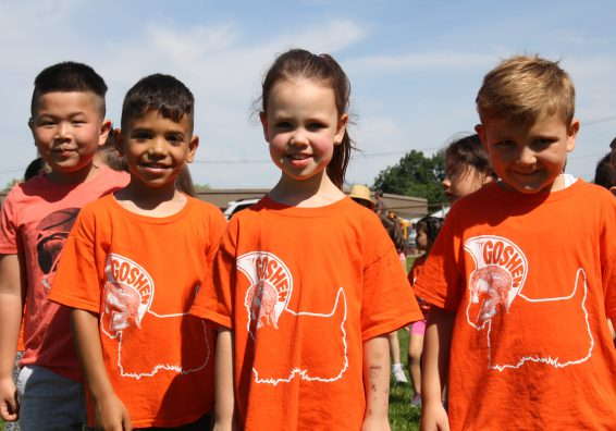 four Scotchtown students standing in a field smile directly at the camera. They are sporting their orange, field day t-shirts.