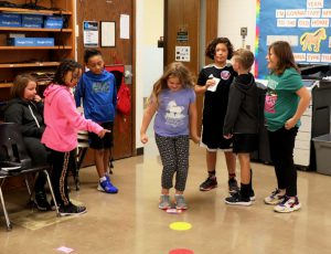 A group of students stand by while another jumps through bright colored dots scattered on the classroom floor.