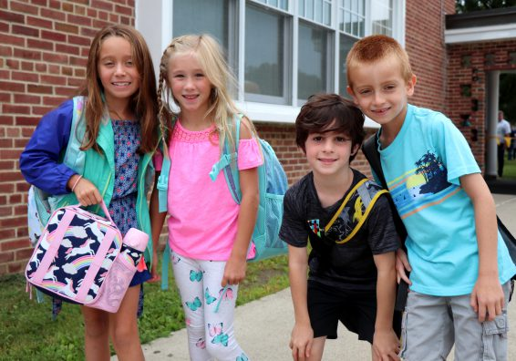Four students with backpacks pose for the camera outside the school building.