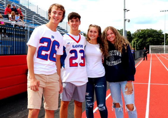 Four high school students pose for the camera while standing on the school's athletic track. Two are wearing Gladiator jerseys.