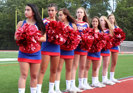 Varsity cheerleaders holding their pom poms line at the edge of the turf field.