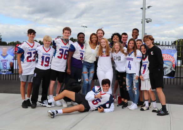 A group of high school students, some wearing Gladiator jerseys, pose outside the stadium.