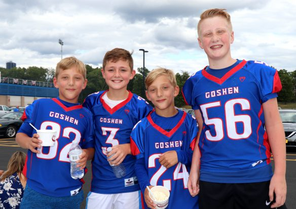 Four students wearing Goshen jerseys stand in high school parking lot outside the stadium during the inauguration of the turf field. Two are eating ice cream.