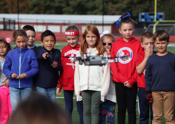 A group of elementary students out in a school field are watching a drone hover in front of them.
