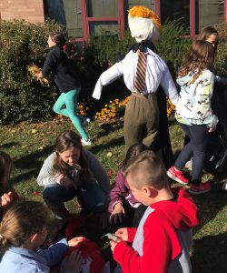 Students and scarecrows on a school lawn.