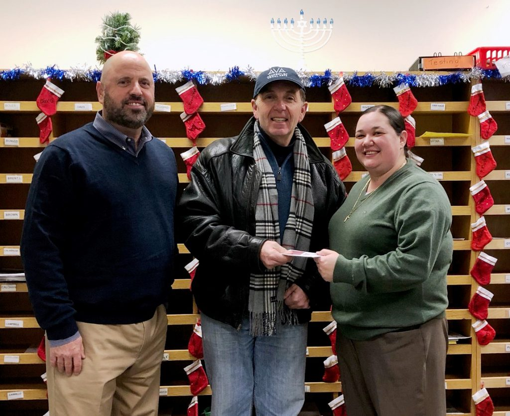 On behalf of the Goshen Rotary Club, President Mark Gargiulo (center) presented a monetary holiday gift to CJ Hooker Middle School Principal, Heather Carman, and Assistant Principal, Bob Syracuse. The funds will be used to brighten the holidays of families in the school community.