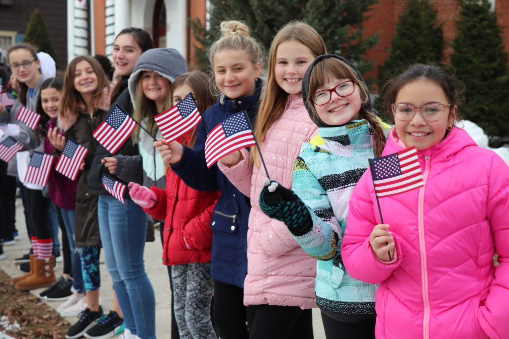 Students lined up on a sidewalk wave small American flags