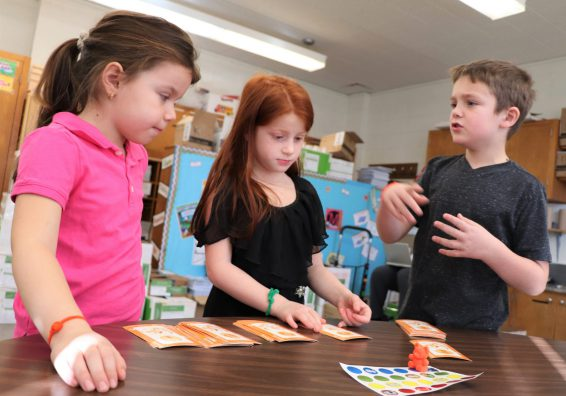 Three first-graders work together on a project