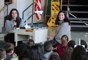 Two teachers presenting to a student assembly.