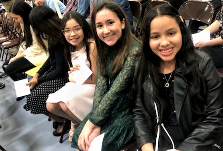 Three students sitting in a crowded auditorium smile at the camera during an awards ceremony.