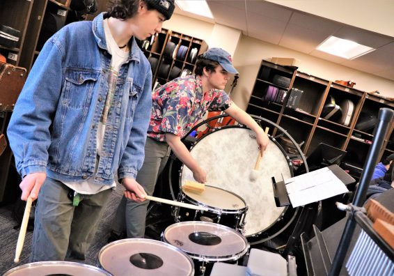 Two high school students playing drums in the music room