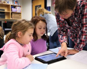 Teacher points at Chromebooks as two students look at it.