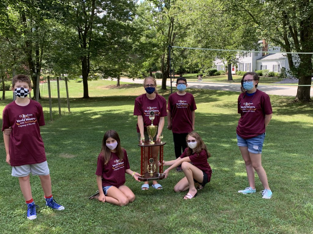 Group of socially distanced masked students with trophy