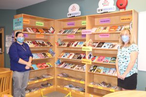 CJH Principal Heather Carman and Library Media Specialist Christine Banuls with shelves of books.