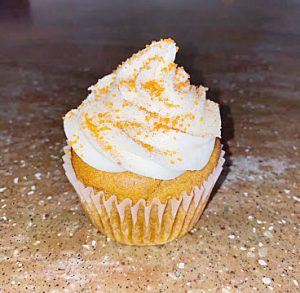 Yellow cupcake with white frosting and yellow sprinkles