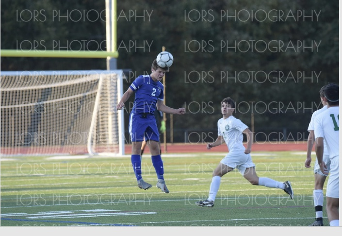 Soccer player heads the ball away from the goal