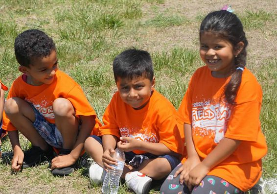 Three students sitting in the grass wearing bright orange t-shirts