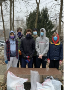Teens wearing masks stand behind white trash bags filled with litter