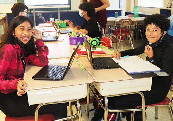 Two students sitting at desks facing each other on laptops smiling at camera