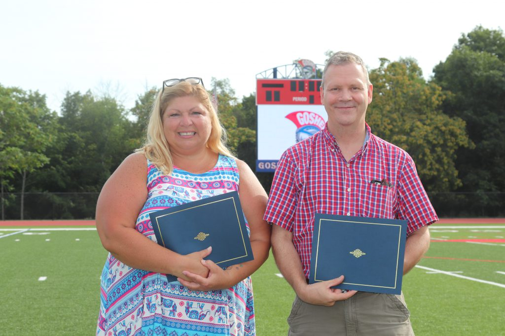 Two adults holding certificates smiling